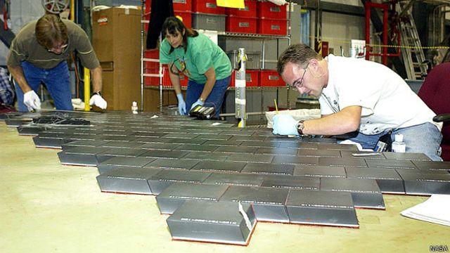 Специалисты НАСА работают над обшивкой шаттла