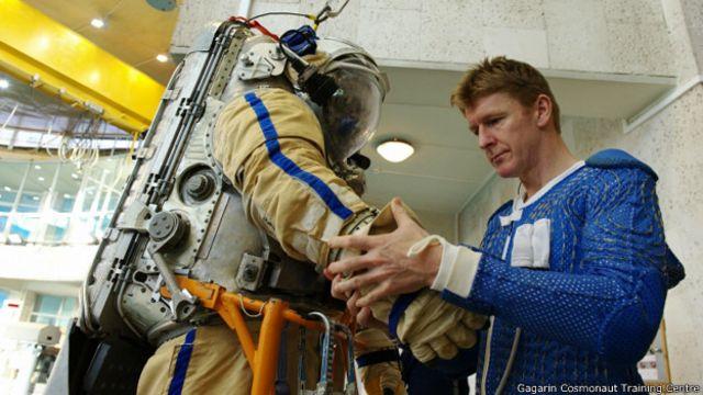 Американский астронавт изучает российский скафандр