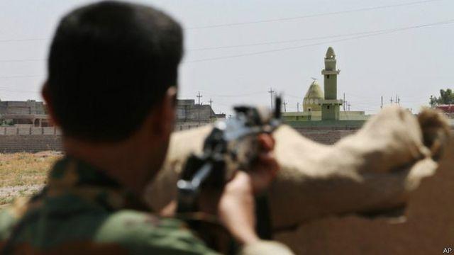 Um combatente curdo assiste ao posicionamento do ISIS em Tuz Khormato, no Iraque (AP)