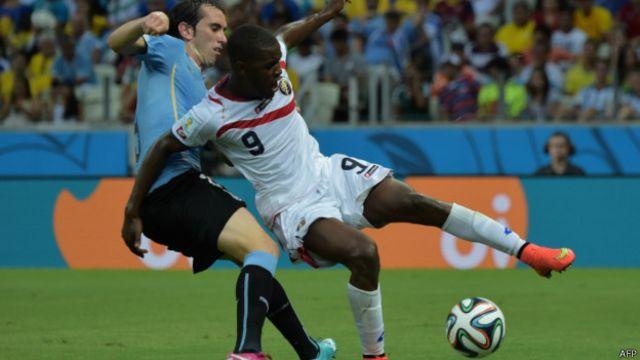 Pemain Kosta Rika, Joel Campbell (kaos putih), berduel dengan pemain belakang Uruguay.