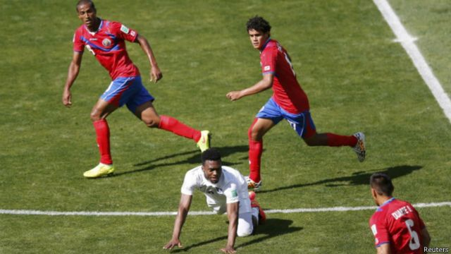 Pemain Kosta Rika (kaos merah) mengepung pemain Inggris di babak penyisihan grup.