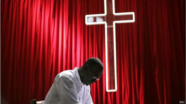 Священник молится на фоне креста