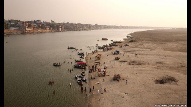 مجموعة من الهندوس يتجمعون عند نهر الغانج في مدينة فاراناسي المقدسة للسباحة والعبادة.