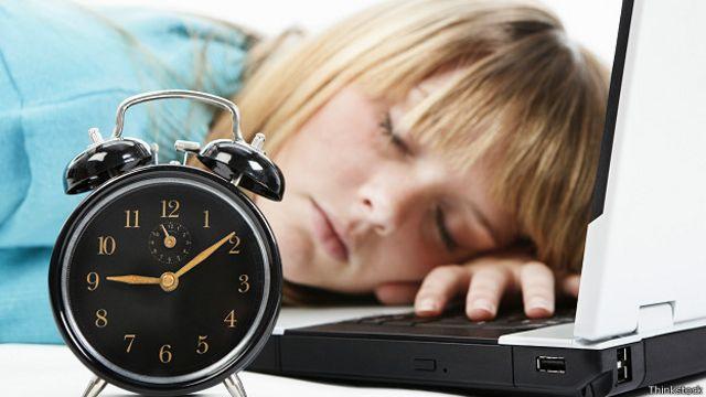 Девушка спит за столом рядом с будильником