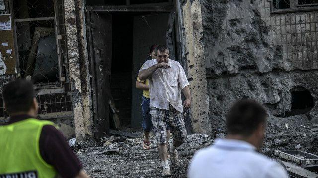 Чоловік біля зруйнованого будинку
