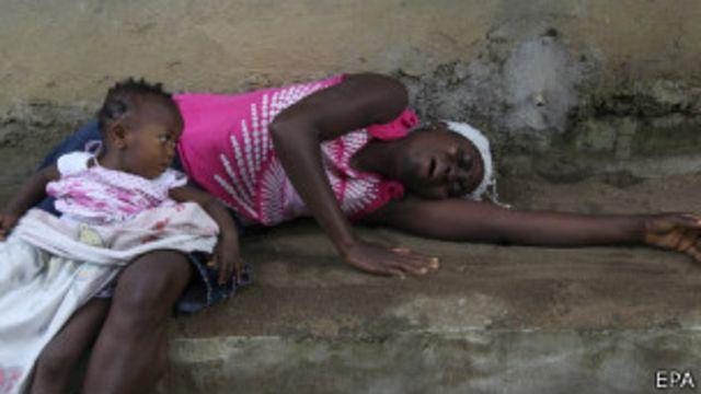 Mujer llora a pariente fallecido por ébola.
