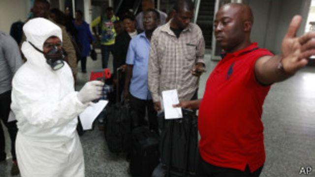 Funcionarios de Salud controlan la temperatura de los pasajeron en el aeropuerto internacionald de Nigeria.