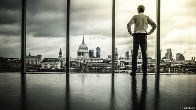 Бизнесмен перед огромным окном с видом на Лондон