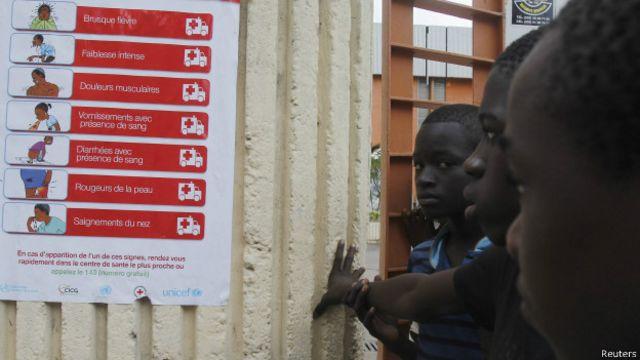 Niños miran cartel con información sobre prevención del ébola en Sierra Leona