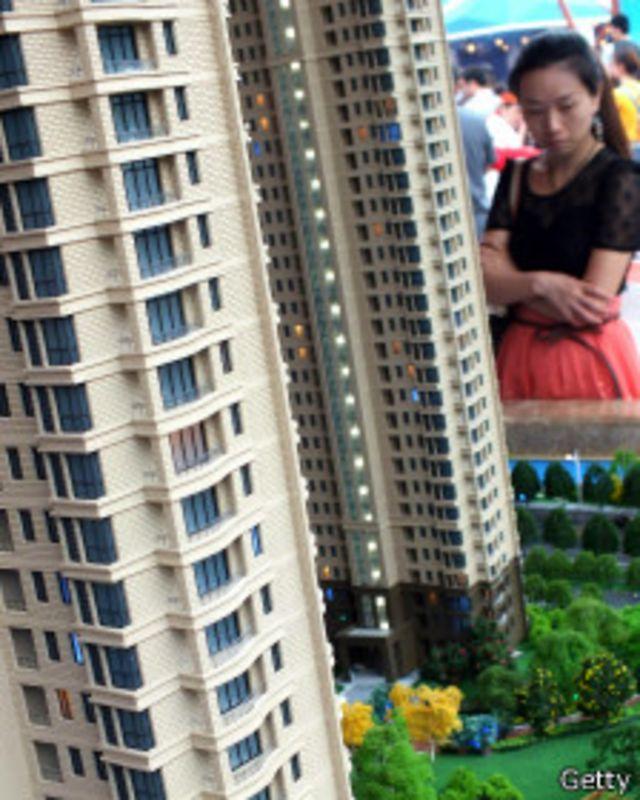Mujer china frente a maqueta de vivienda.