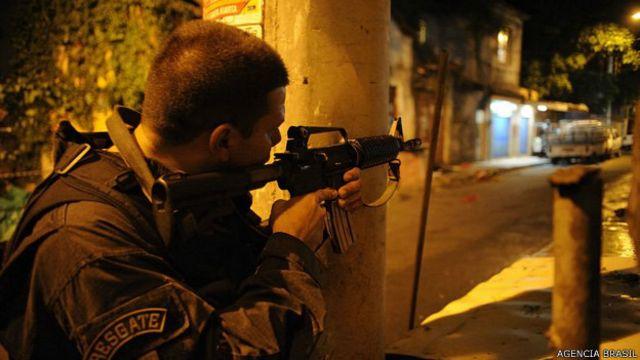 Policía apunta su fusil en una comunidad de Río de Janeiro.