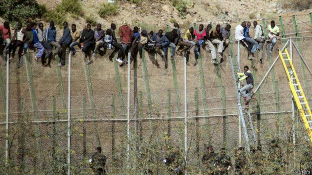 Migrantes encaramados en la valla
