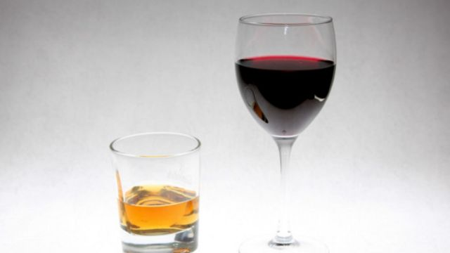 a glass of whisky and a glass of red wine