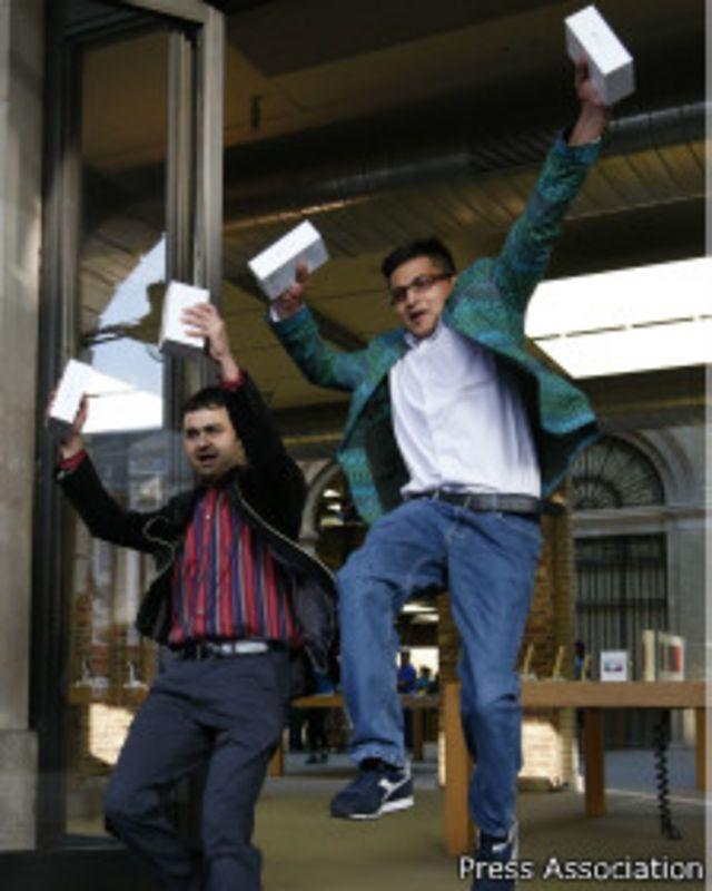Dos clientes celebran en Londres haber conseguido comprar un iPhone 6 el primer día que salió a la venta.