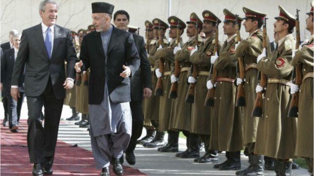 زمینه سازی برای تشکیل حکومت در افغانستان توسط جنگنده های آمریکایی صورت گرفت. افغانستان در دوران حکومت آقای کرزی روابط پر فراز و نشیبی با آمریکا داشت. این تصویر از سفر سرزده جورج دبلیو بوش رئیس جمهوری سابق آمریکا به کابل در سال ۲۰۰۶ است.