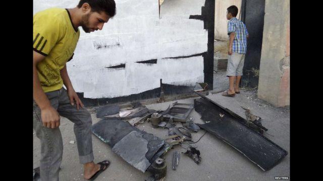الرقہ میں دولتِ اسلامیہ کا کہنا ہے کہ فضائی حملوں میں شامل ایک ڈرون گر کر تباہ ہو گیا ہے۔ تصویر میں ایک شخص ڈرون کے ملبے کا جائزہ لے رہا ہے۔