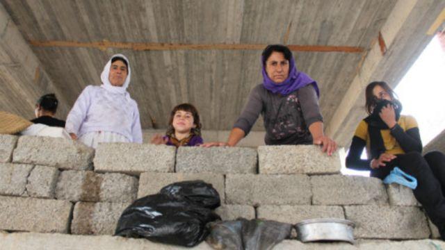 نساء من الإيزيديين يطللن من مبنى غير مكتمل