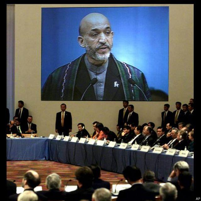 حامد کرزی حال سخنرانی در اجلاس توکیو برای جلب کمک برای بازسازی افغانستان با حضور نمایندگان شصت کشور و سازمان بینالمللی در ماه ژانویه ۲۰۰۲ .
