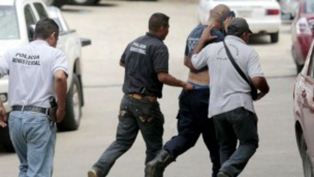 Un policía de Iguala es escoltado para declarar por el ataque a estudiantes. Foto: AFP/Getty