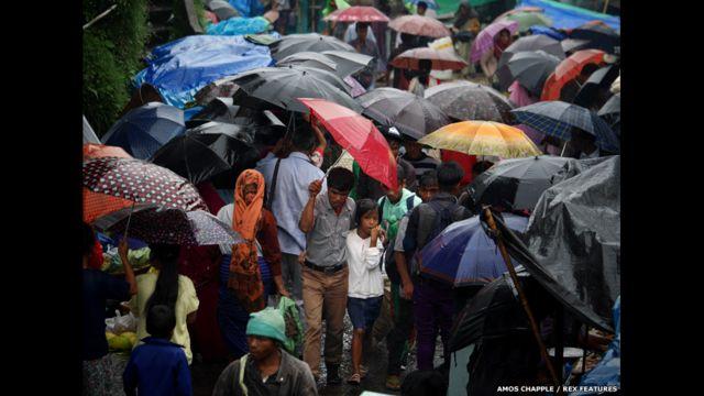 Moradores andam sob guarda-chuvas em Mawsynram. (foto: Amos Chapple / Rex Features)