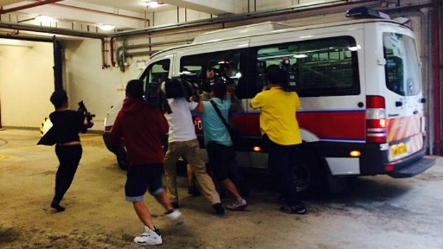 Kendaraan yang membawa tersangka pembunuh dua perempuan di Hong Kong dikerumuni wartawan.