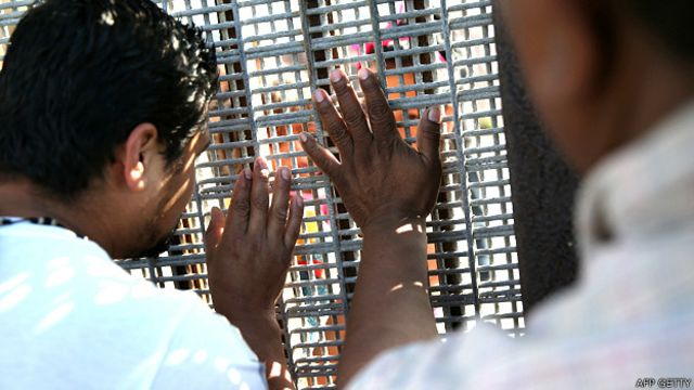 Personas a ambos lados de una valla en la frontera entre EE.UU. y México