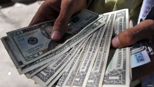 Человек держит в руках доллары