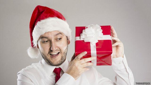 Un ejecutivo con sombrero de Papá Noel y una caja de regalos