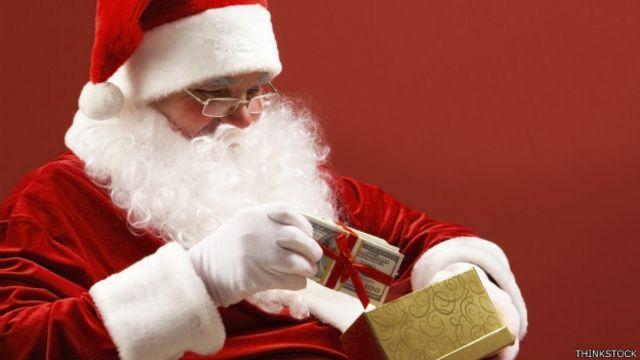Santa Claus pone dinero en una cajita de regalo