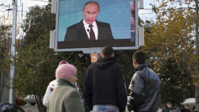 Перехожі у Севастополі дивляться на великому екрані виступ президента Росії у жовтні