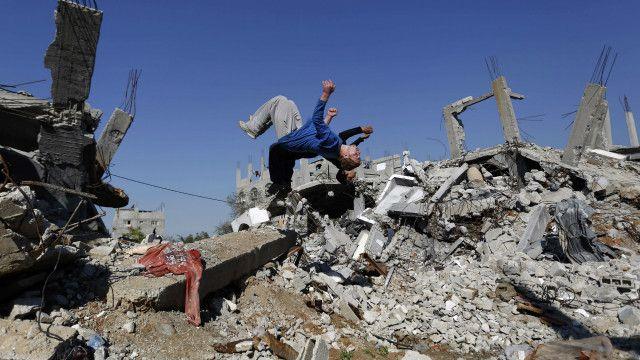 صبي فلسطيني يلعب على أنقاض منزل تهدم خلال الحرب الأخيرة في غزة.