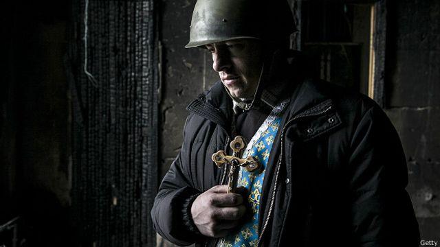 Украинский священник в каске держит крест