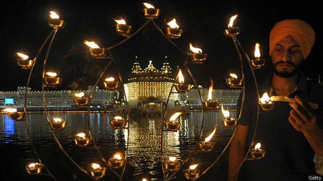 Индийский сикх зажигает свечи во время праздника Банди Чхор Дивас, или Дивали