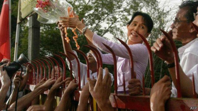 Aung San Suu Kyi berdiri dari balik gerbang rumahnya saat dibebaskan pada 2010 lalu.