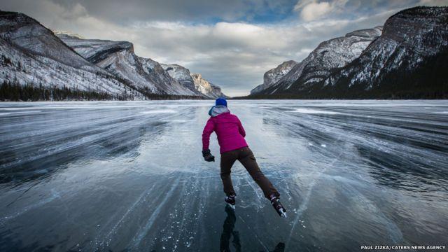Una persona patina en un lago helado en Canadá. Fotografía: Paul Zizka.