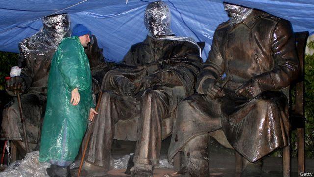 """Рабочий моет памятник """"Большой тройке"""" перед открытием"""