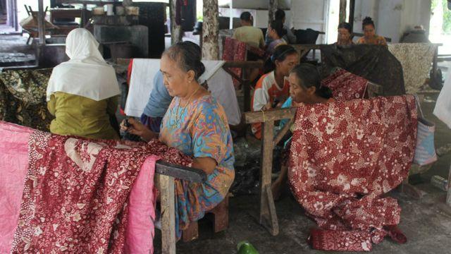 Para pengrajin batik di pabrik Sekar Kencana tengah menyelesaikan batik tulis.