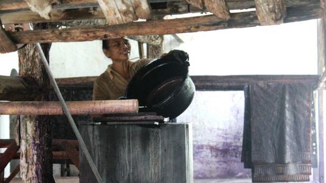 Seorang pengrajin menuangkan bahan pewarna untuk batik