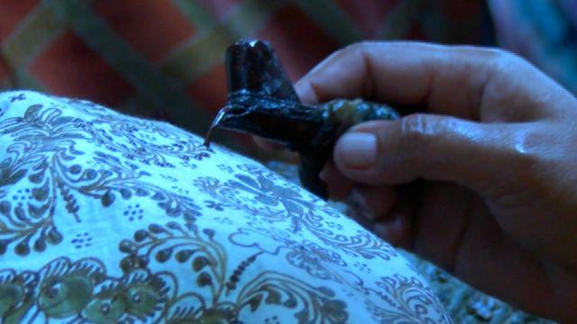 Pengrajin batik menempelkan lilin atau malam pada sehelai batik
