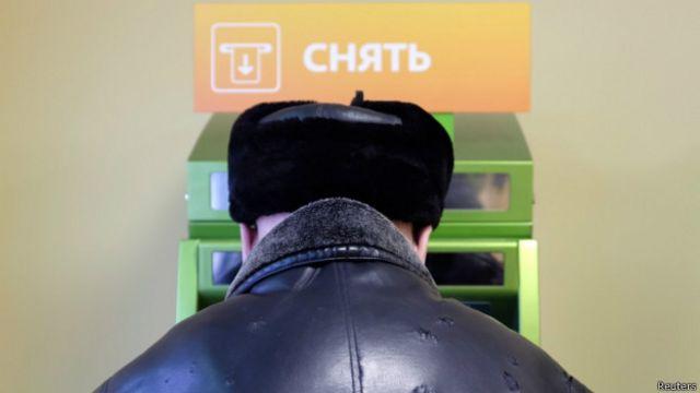 Мужчина снимают деньги в банкомате