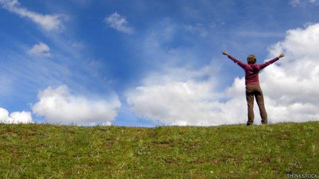 Una persona en un campo con los brazos extendidos