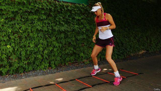 Los estiramientos dinámicos forman parte del calentamiento del cuerpo antes de hacer ejercicio, como lo hace la tenista danesa Caroline Wozniacki.