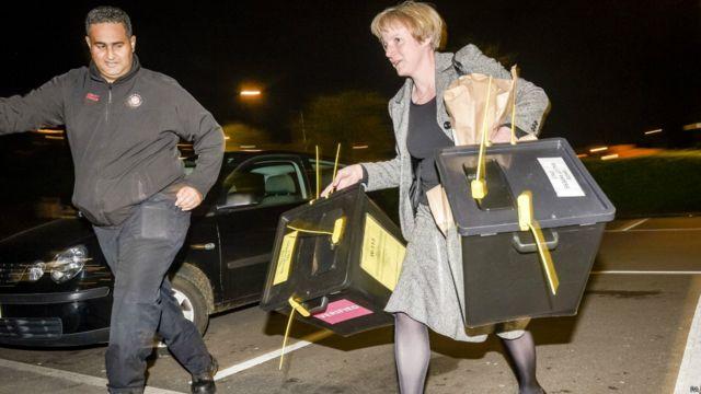 Petugas membawa dua kotak suara pertama dari kawasan pemilihan Bristol yang tiba di tempat penghitungan suara wilayah di City Academi Bristol.