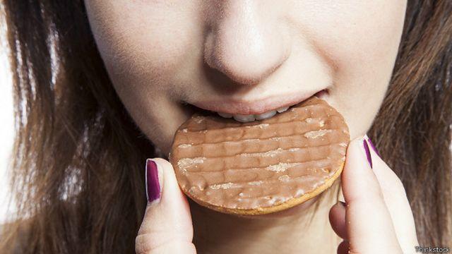 Девушка надкусывает печенье
