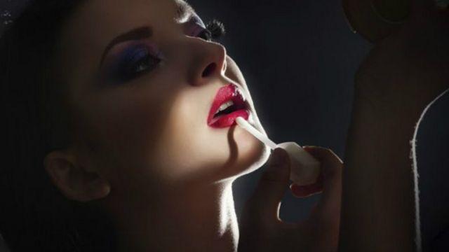 mujer pintandose los labios