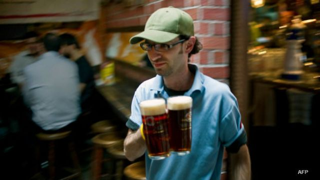 Un barman sirve tarros de cerveza en México
