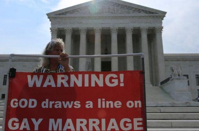 """""""¡Peligro! Dios no tolera el matrimonio gay"""", reza la pancarta que llevaba esta mujer."""