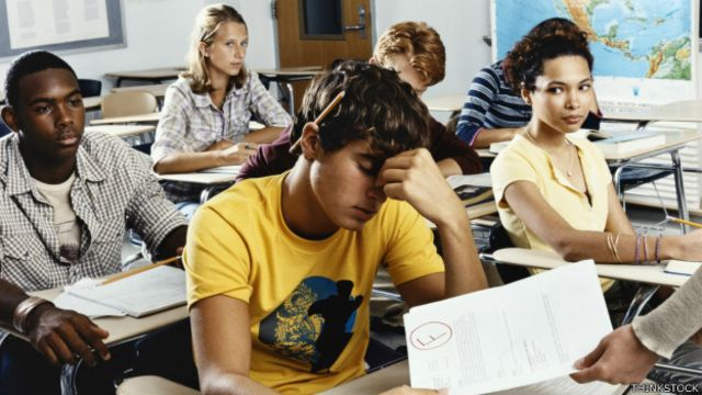 Estudiantes recibiendo exámenes corregidos