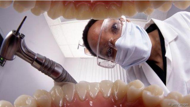 Un dentista que se acerca con instrumentos