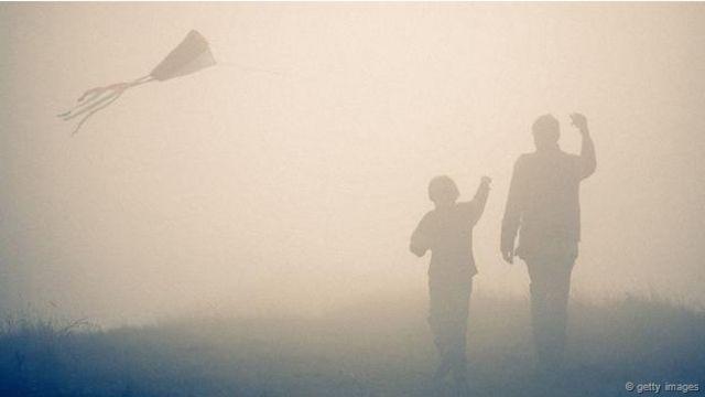 Un hombre y un niño vuelan una cometa